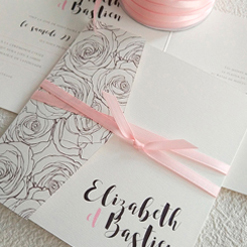 wedding invite in pink and grey with a few flowers